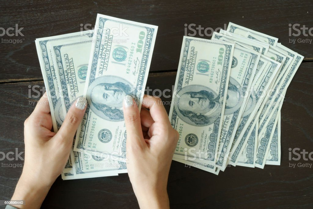 close up of woman counting money at home stock photo