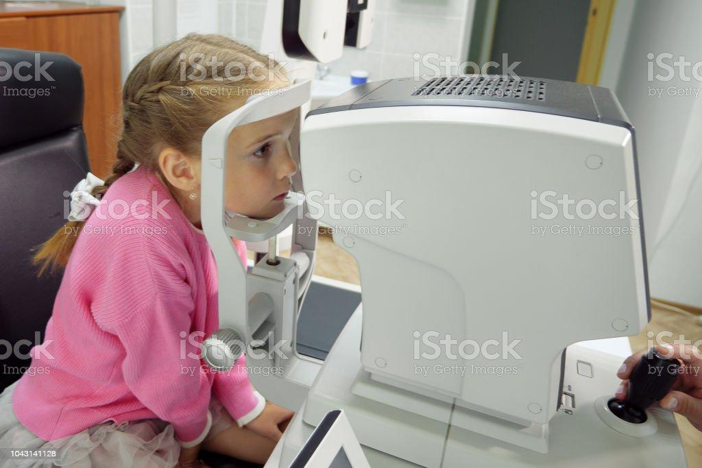 Nahaufnahme von Frau Doktor arbeiten mit der Maschine Refraktometer. Ein kleines Mädchen mit ihren Augen getestet – Foto