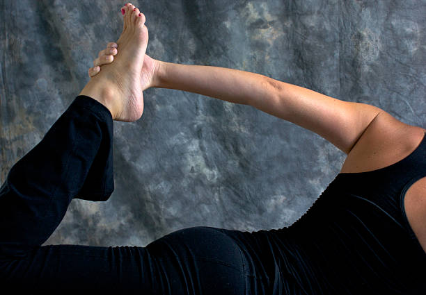 close up of woman doing half bow yoga pose stock photo