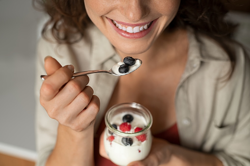 Close up of of smiling woman hands having a healthy breakfast at home with fruit and yogurt. Cheerful girl tasting yoghurt with blueberries and raspberries. Joyful woman enjoy fresh yogurt for lunch, wellbeing and diet concept.