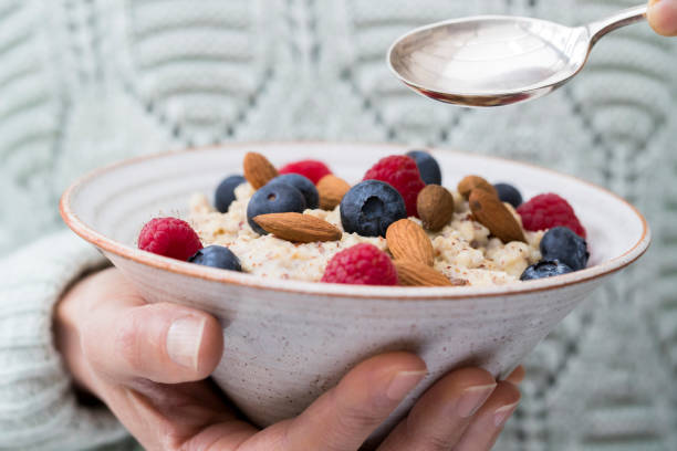 Close Up Of Woman Eating Bowl Of Porridge with Fruit And Nuts For Healthy Breakfast Close Up Of Woman Eating Bowl Of Porridge with Fruit And Nuts For Healthy Breakfast oatmeal stock pictures, royalty-free photos & images