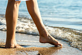 Close up of woman feet walking barefoot on sand leaving footprints on golden beach. Vacation, travel and freedom concept. People relaxing in summer.