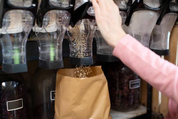 Nahaufnahme der Frau Füllung Papiertüte mit Reis aus Dispenser für Getreide und Getreide in Kunststoff kostenlos Lebensmittelgeschäft – Foto