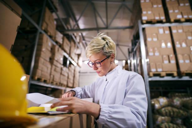 nahaufnahme von frau papierkram stehen im lager zu füllen. im hintergrund regale mit kästen. - umzug checkliste stock-fotos und bilder