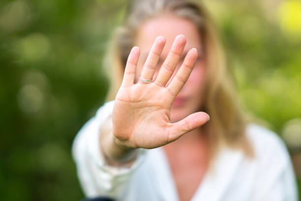 Close up of woman gesturing stop sign, focus on hand stock photo