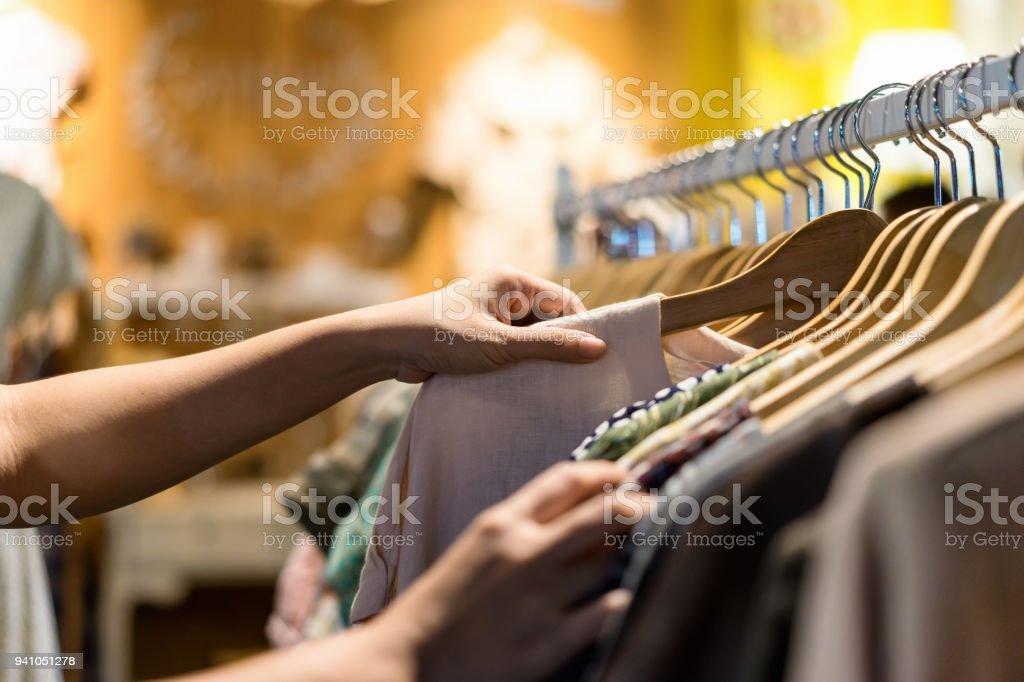 Close up van vrouw hand kiezen spaarzaamheid jonge en goedkope t-shirt kleding in de winkel, zoeken of kopen goedkope katoenen shirt op rek hanger op rommelmarkt, kraam winkelen kleding mode concept - Royalty-free Alleen volwassenen Stockfoto