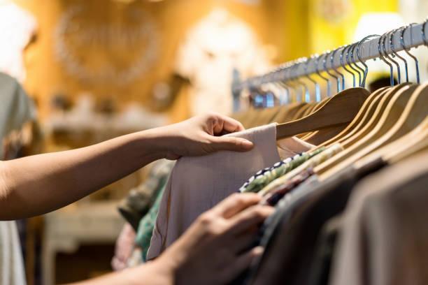 bliska ręka kobiety wybierając oszczędności młodych i zniżki t-shirt ubrania w sklepie, wyszukiwanie lub zakup taniej bawełnianej koszuli na wieszaku na pchlim targu, stoisko zakupy odzież moda koncepcji - odzież zdjęcia i obrazy z banku zdjęć