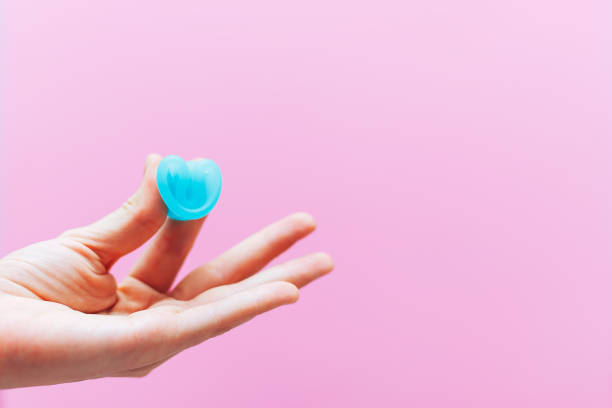 close up of woman hand folding menstrual cup showing how to use, c form. women health concept, zero waste alternatives - coppa mestruale foto e immagini stock