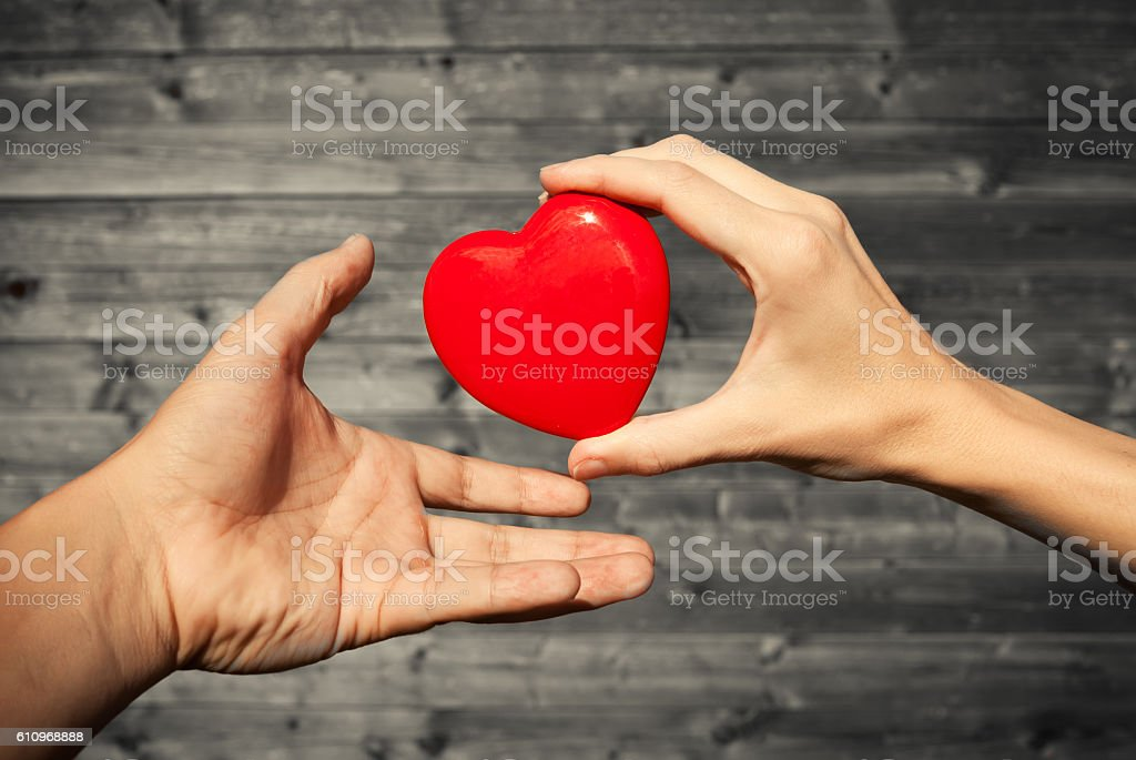 Close up of woman hand giving heart to man stock photo