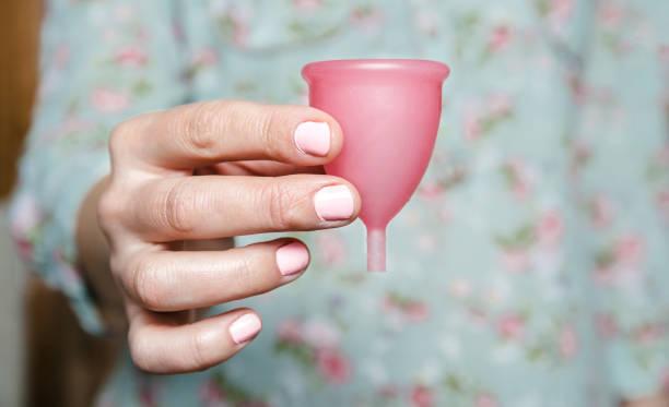 close up of woman hand holding menstrual cup - coppa mestruale foto e immagini stock