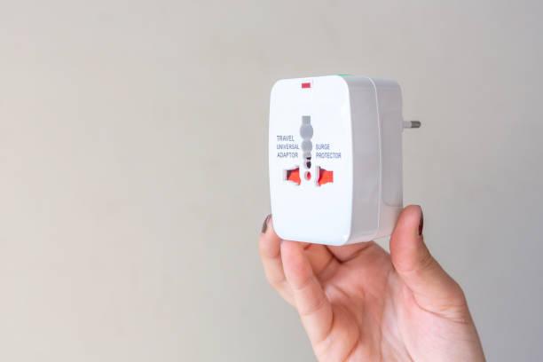 nahaufnahme der frau hand hält universelle steckdose stecker adapter, isoliert auf weißem hintergrund. wird verwendet, um steckdosen weltweit zu verbinden. konzept von sollution, reisen und technologie. - adapter stock-fotos und bilder