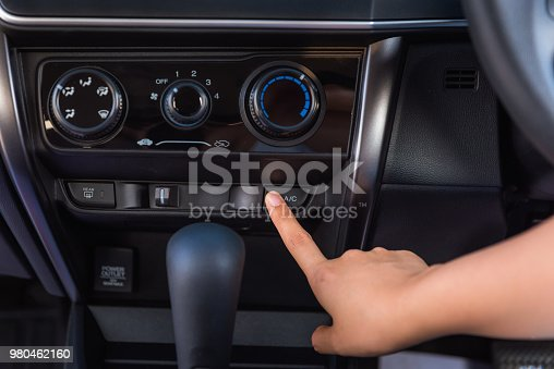 istock Close up of woman hand pressing turn on air-conditioner button a car 980462160