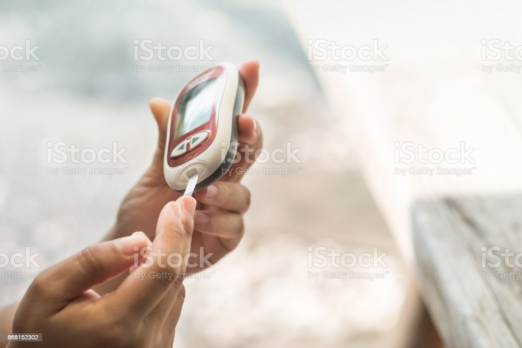Close up of woman hands checking blood sugar level by Glucose meter...