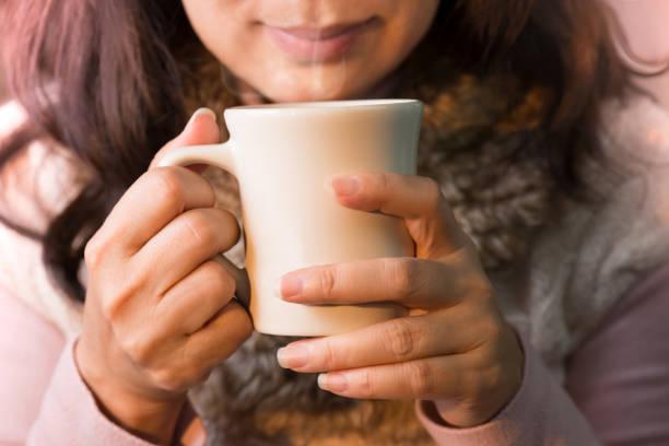close up of woman hands holding a cup of coffee. - gesichtertassen stock-fotos und bilder