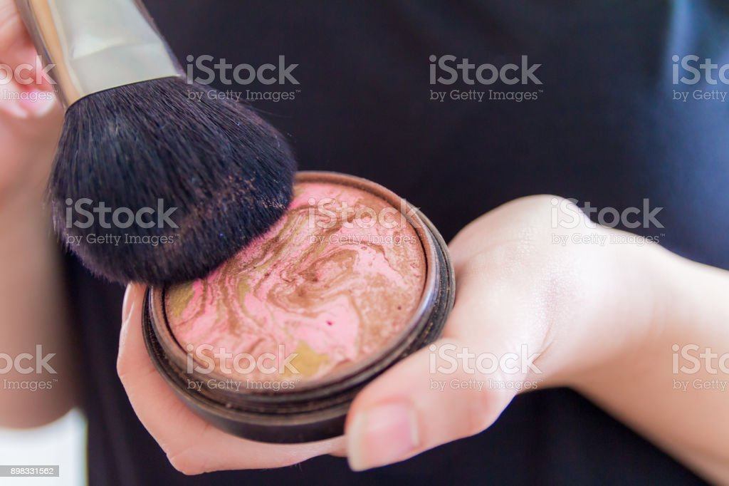 Close up of woman hands holding makeup bronzer stock photo