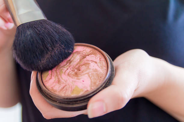 Close up of woman hands holding makeup bronzer stock photo