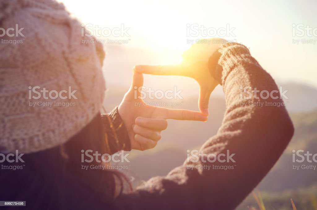Nahaufnahme von Frau Hände Frame Geste mit Sonnenaufgang am Berg, Weiblich, die Erfassung der Sunrise, Zukunft planen, Sonnenlicht im Freien. – Foto