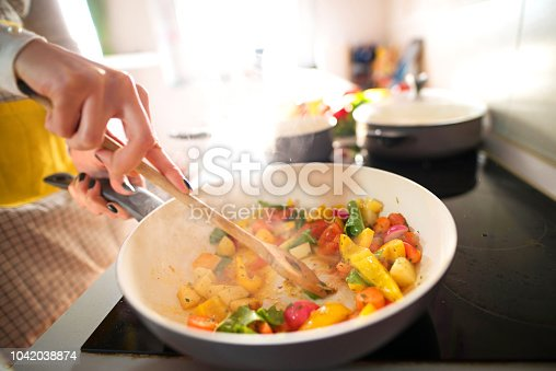 Close up of woman hands mixing food in cooking pan.