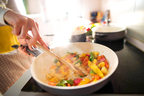 여자 손에 음식 냄비 요리에 혼합의 닫습니다. - 요리하기 식품 상태 뉴스 사진 이미지
