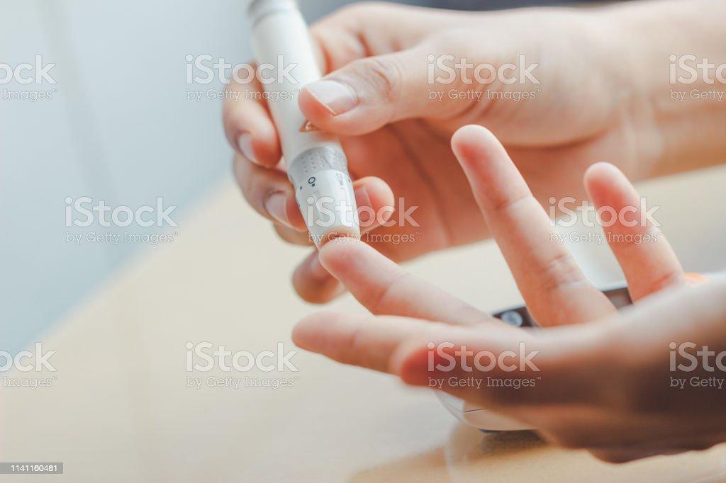 Nahaufnahme der weiblichen Hände mit Lanyet am Finger, um den Blutzuckerspiegel mit Glukose-Meter mit Hilfe von Medizin zu überprüfen - Lizenzfrei Analysieren Stock-Foto