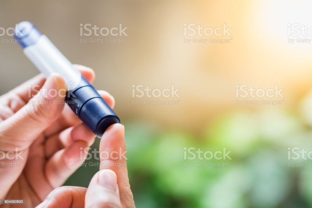 Close up of woman hands using lancet on finger to check blood sugar level by Glucose meter using as Medicine, diabetes, glycemia, health care and people concept. stock photo