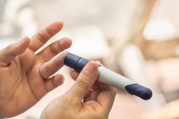 nahaufnahme von frau hände mit lanzette auf finger, um blutzuckerspiegel durch blutzuckermessgerät mit als medizin, diabetes, glycemia, gesundheitsversorgung und menschen konzept zu überprüfen. - blutzuckermessung stock-fotos und bilder