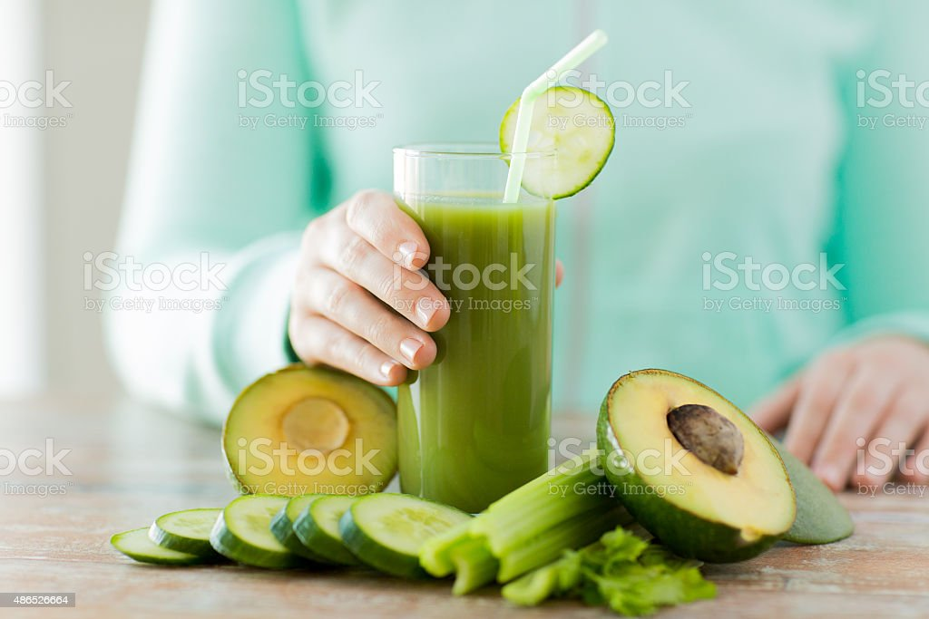close up of woman hands with juice and vegetables stock photo