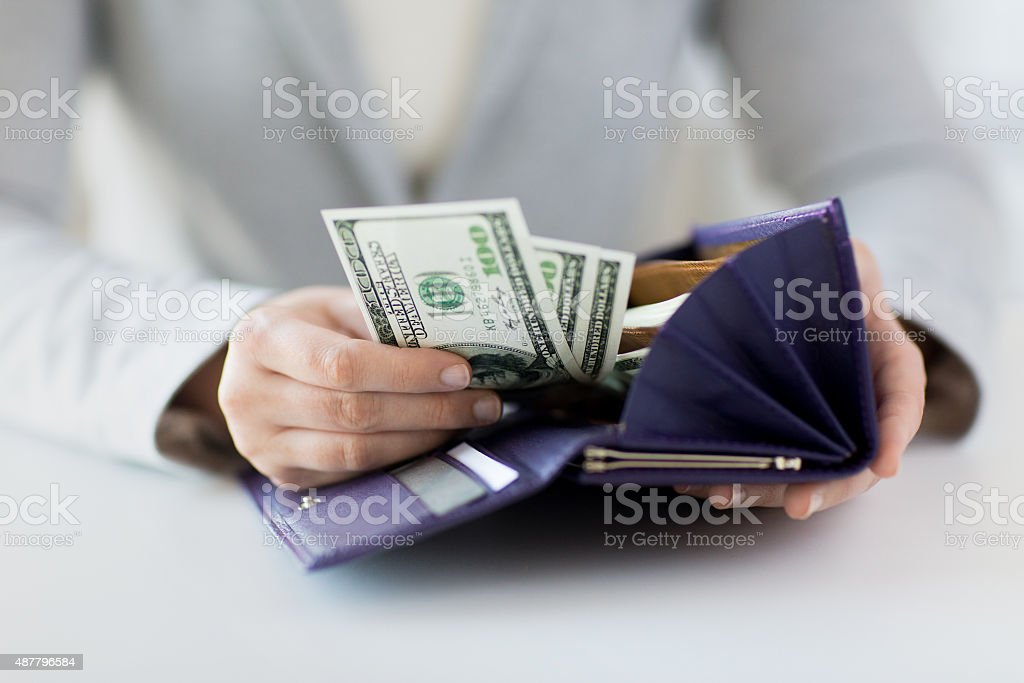 close up of woman hands with wallet and money stock photo