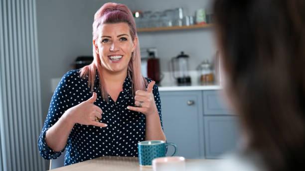 手話を使って自宅で会話する女性のクローズアップ - disabilitycollection ストックフォトと画像