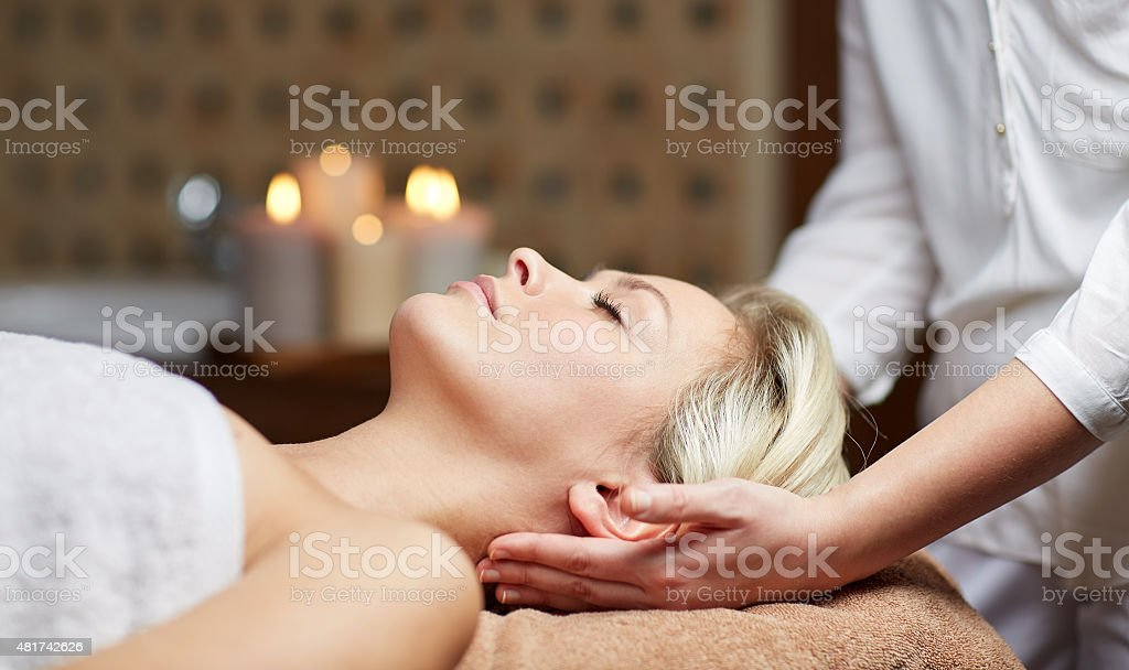 close up of woman having face massage in spa stock photo