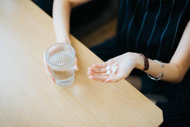 nahaufnahme der frau hält ein glas wasser und medikamente in der hand - schmerzmittel stock-fotos und bilder