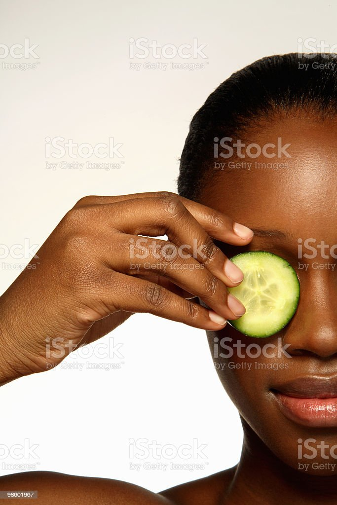 Close up of woman holding cucumber slice on eye  royalty-free stock photo