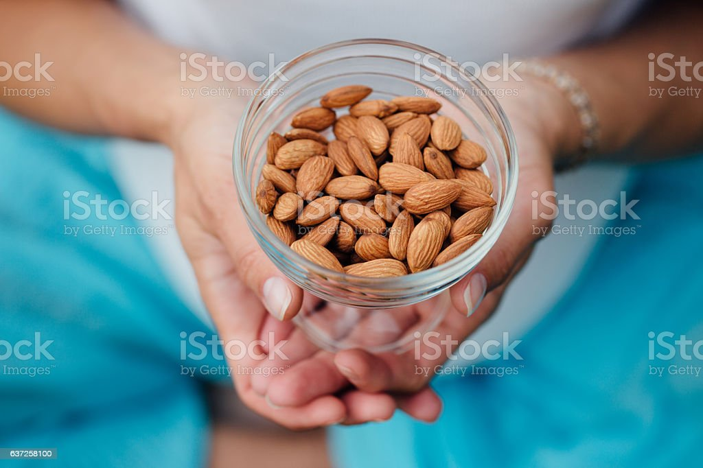 Close Up Of Woman Holding glass bowl with Almonds nuts. stock photo