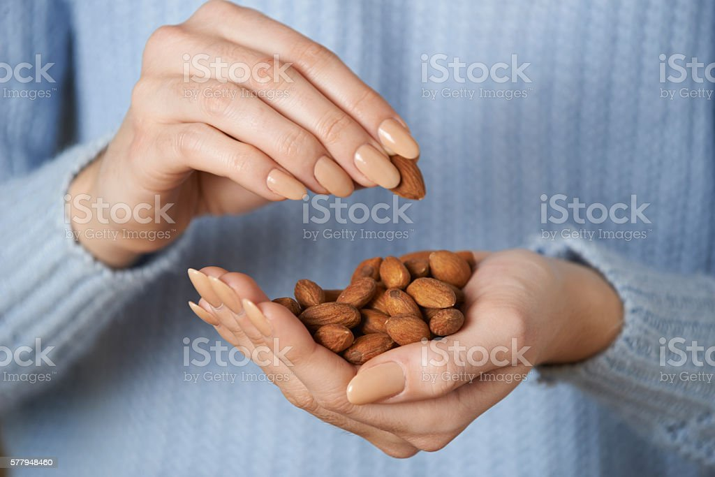 Close Up Of Woman Holding Handful Of Almonds stock photo