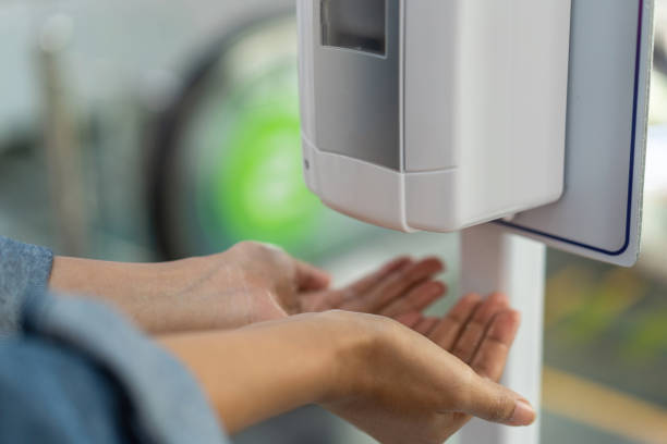 Close up of woman holding hands under automatic sanitiser dispense