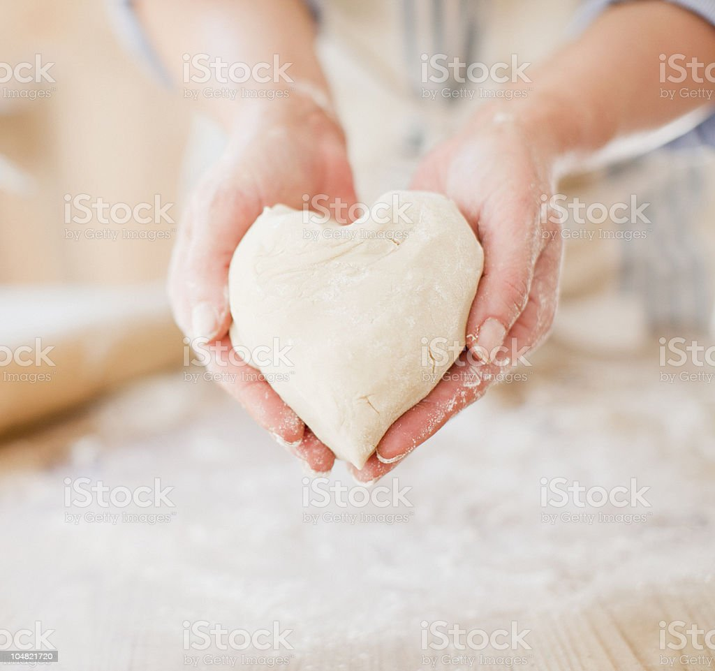 Close up of woman holding heart-shape dough stock photo