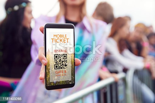 Close Up Of Woman Holding Mobile Phone Screen To Camera As She Arrives At Entrance To Music Festival