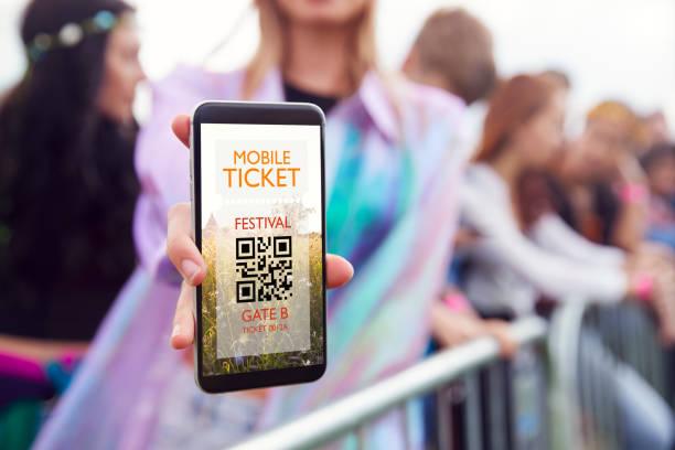 Nahaufnahme der Frau hält Handy-Bildschirm zur Kamera, als sie am Eingang zum Musikfestival ankommt – Foto