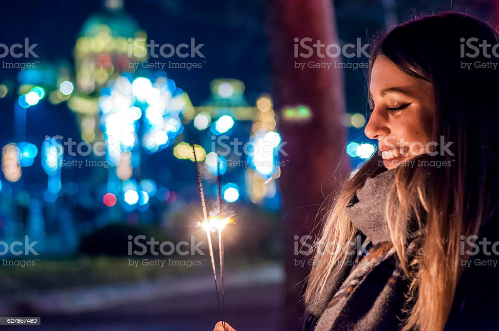 Close up of woman holding sparkler on the street. stock photo