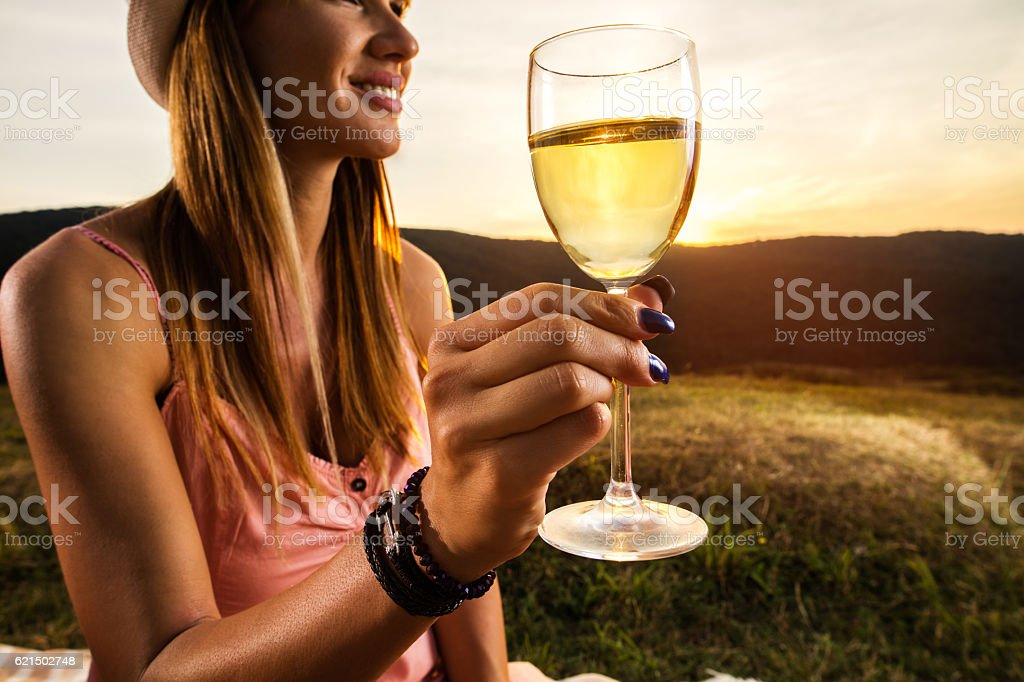 Close up of woman holding wineglass at sunset. photo libre de droits