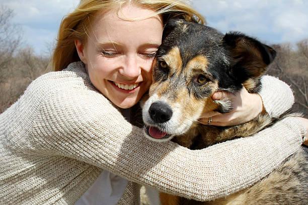 Close up of Woman Hugging German Shepherd Dog stock photo