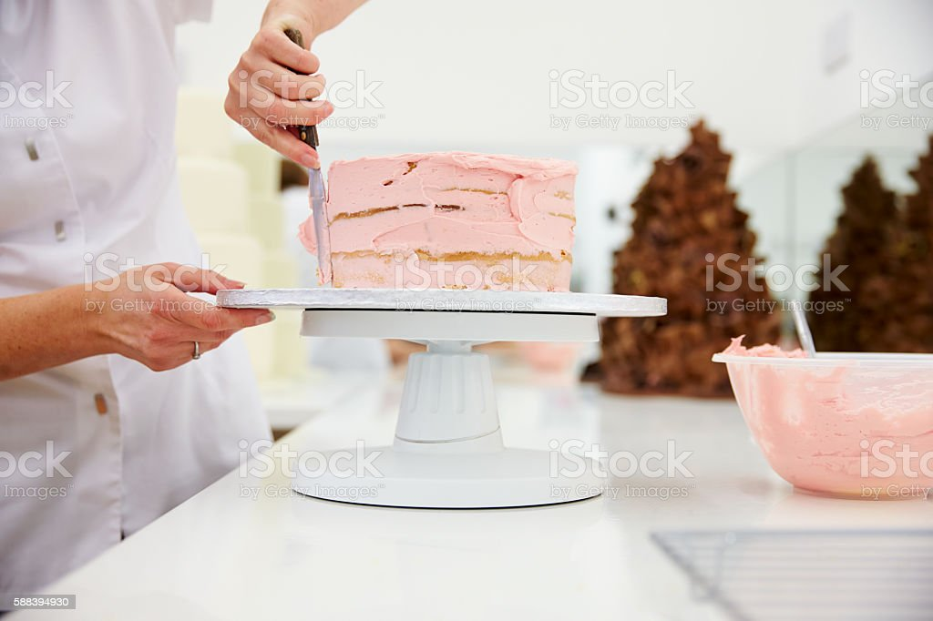 Close Up Of Woman In Bakery Decorating Cake With Icing stock photo