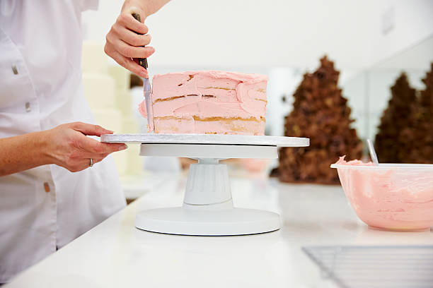 Close Up Of Woman In Bakery Decorating Cake With Icing Close Up Of Woman In Bakery Decorating Cake With Icing decorating a cake stock pictures, royalty-free photos & images