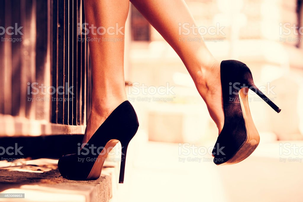 Close up of woman in black heels balanced on a step stock photo