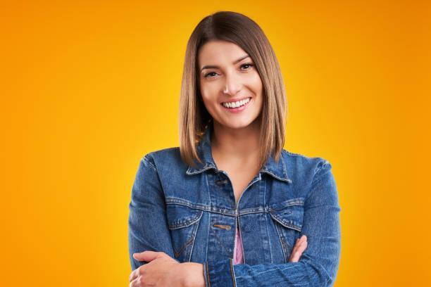 Nahaufnahme der Frau in Jeansjacke mit Blick auf die Kamera über gelbem Hintergrund – Foto