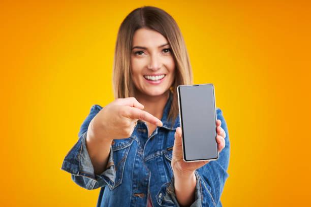 Nahaufnahme der Frau in Jeansjacke mit Smartphone über gelbem Hintergrund – Foto