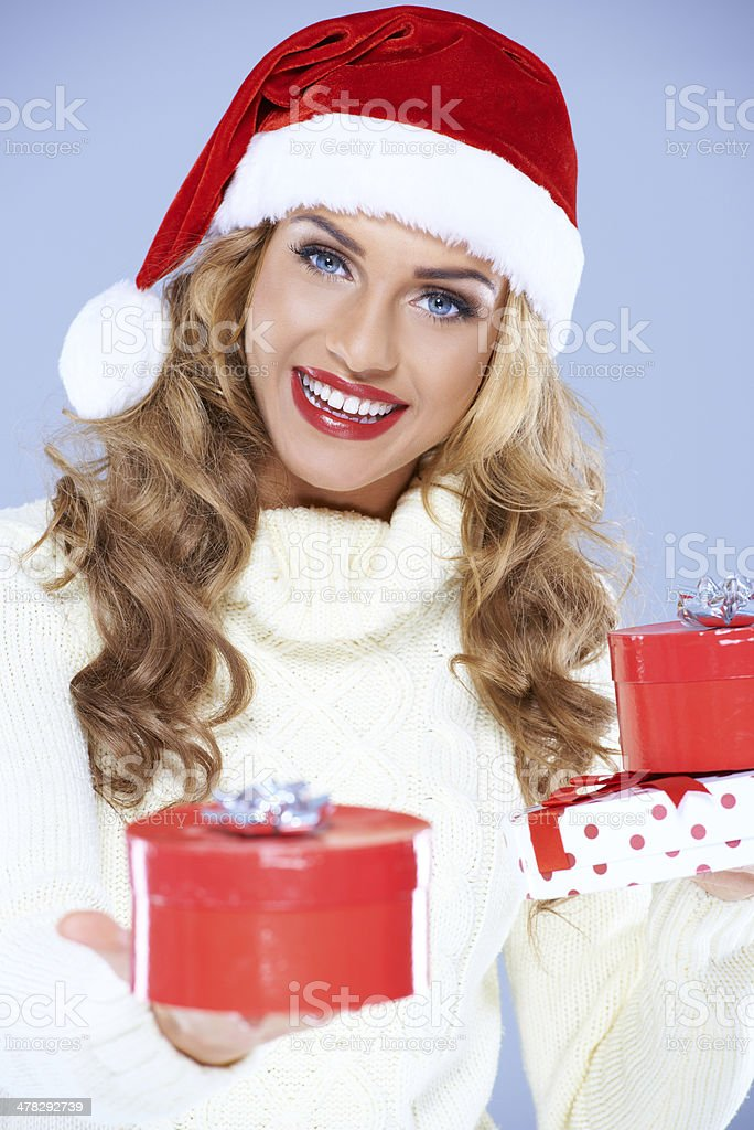 Close up of woman in Santa hat holding Christmas gifts royalty-free stock photo