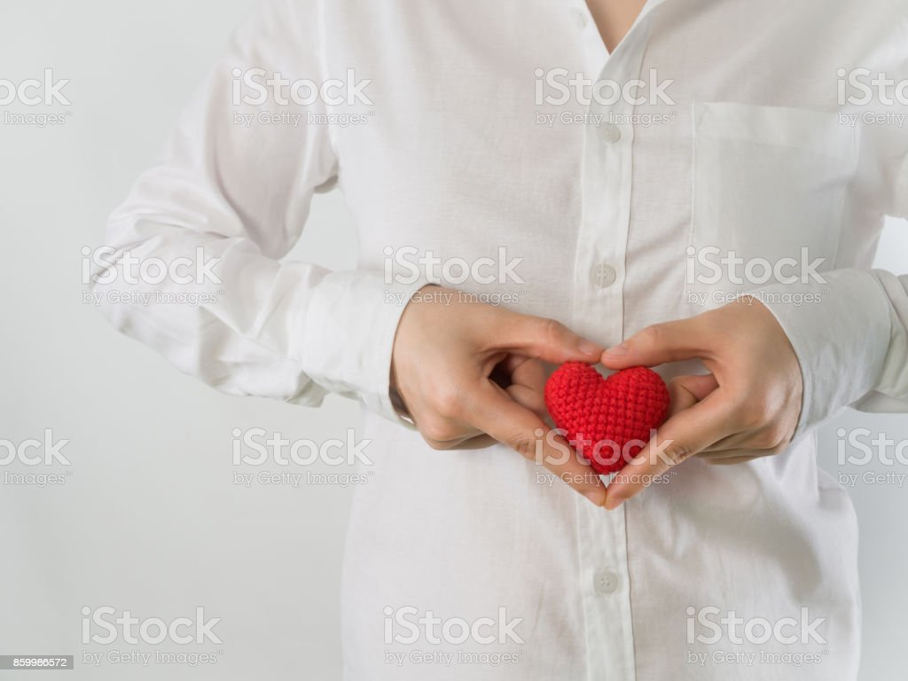 close up of woman in white shirt  holding red shape sing on isolated background. stock photo