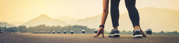 close up of woman leg in running start to reach the goal. jogging workout and sport healthy lifestyle concept. proportion of the banner for ads. - corsa su pista femminile foto e immagini stock