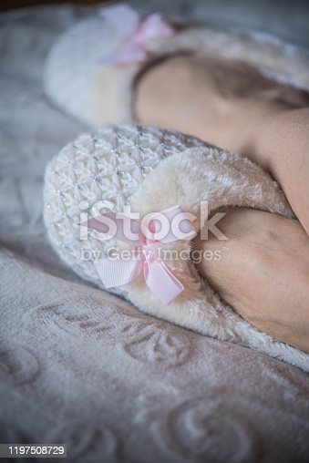 Close Up of  Woman Legs in Fluffy Slippers on the Bed